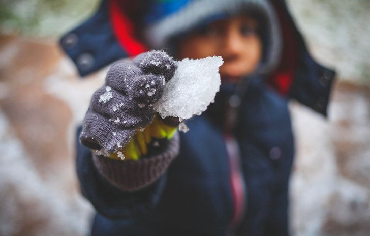 Child holding snow
