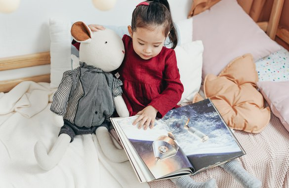 Girl reading to teddy